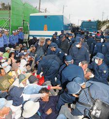 ゲート前に座り込む市民を立たせて引き抜く警察官たち=2015年11月4日午前7時1分、名護市辺野古のキャンプ・シュワブ前(沖縄タイムス提供)