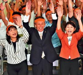 当確の報を受け、万歳で喜ぶ玉城デニー氏(中央)=22日午後8時すぎ、沖縄市安慶田の選挙事務所