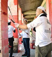 柱のペンキ塗り替え作業をする参加者