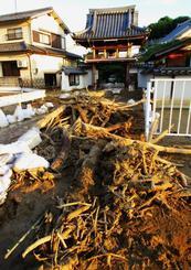 榎川の氾濫で、流れ着いて橋の上に片付けられた流木や土砂=11日、広島県府中町(嘉陽礼文さん提供)