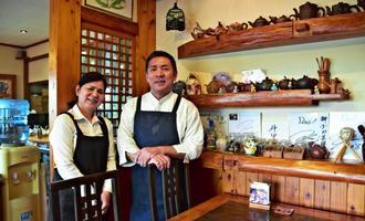 店は店主の金城美好さん(右)、妻の勝江さん夫婦の連携で切り盛りする。シーサーが店内外のあちこちに=南風原町津嘉山