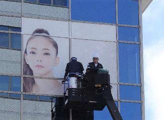 安室奈美恵さんの特大ポスターを設置する作業員たち=午前10時17分、那覇市久茂地・タイムスビル