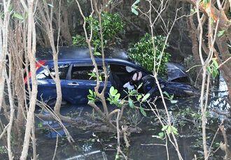 コンビニ駐車場のフェンスを突き破り、沼地に転落した乗用車=23日午後6時ごろ、名護市真喜屋