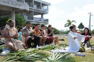 ツカサと共に、伊良部島の神に祈りをささげるクムフラやカギマナフラの大会出演者=6日午前、宮古島市伊良部のホテルてぃだの郷