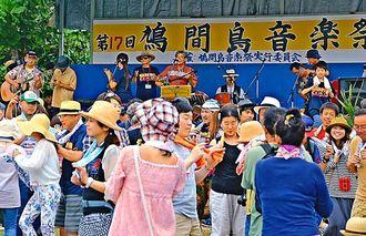 鳩間島の住民らの「鳩間島オールスターズ」の演奏で踊る来場者=竹富町鳩間