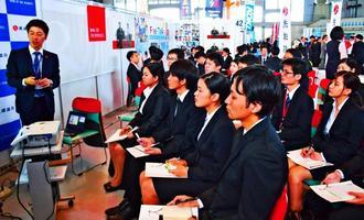 就職フォーラムで企業の人事担当(左端)から説明を受ける学生たち=5日、宜野湾市・沖縄コンベンションセンター