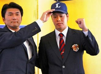 西武へ入団が決まり、記者会見でポーズをとる富士大の多和田真三郎投手(右)=11日、岩手県雫石町
