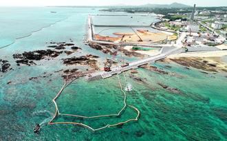 大浦湾側の護岸「K4」(中央左)から沖合に延びる「K8」護岸建設が始まった。作業船がクレーンでつり上げた汚濁防止膜を海上に引き出す=5日午後、名護市(小型無人機で撮影)