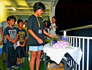 果物や花が置かれたテーブルに線香を立て、対馬丸犠牲者の冥福を祈る南風原の子どもたち=20日午後9時40分、鹿児島県奄美大島沖