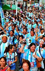 サッカーアルゼンチン代表のユニフォームを着て、にぎやかに行進する県系人