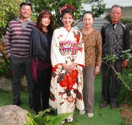 成人式で上原家の女性が3世代受け継ぐ振り袖を着る上原栞奈さん(中央)。右側は祖父・俊光さん、祖母・直恵さん。左側は父・晶也さん、母・信子さん=13日、豊見城市我那覇