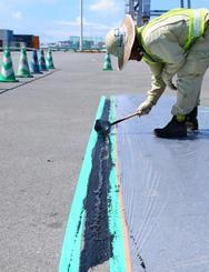 アスファルトで補修する作業員=28日、那覇港(沖縄総合事務局提供)
