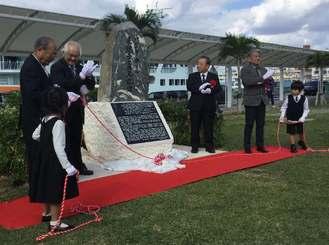 バジル・ホール来琉の記念碑を除幕する関係者=16日、那覇市・泊緑地