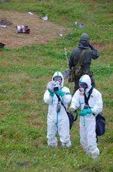 落下物の周辺で汚染状況を調べる県警と陸自=19日、那覇市・陸上自衛隊那覇訓練場