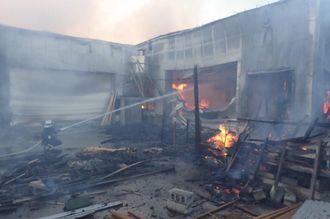 木工所の工場部分の消火を行う消防隊員=1日午後5時29分、糸満市西崎