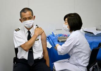 ANAグループが実施した新型コロナワクチンの職場での接種を受けるパイロットの男性=13日午前、羽田空港