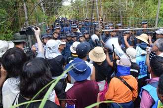 「N1裏」の林道に沖縄防衛局が設けたフェンスをはさみ、ヘリパッド建設に反対する市民らとにらみ合う機動隊員ら=26日午後1時すぎ