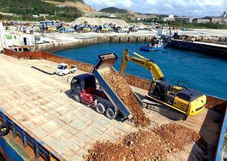 (写図説明)本部港塩川地区に接岸した台船に、土砂を運び込むダンプカー=25日午後3時25分(小型無人機で撮影)