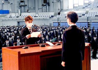 2年生の入学生代表として西田睦学長(手前)に宣誓する伊波翔悟さん=6日、宜野湾市(琉球大学提供)