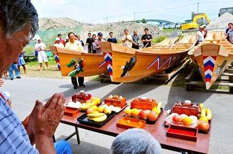 進水式前、ハーリー舟にお供え物をして手を合わせる名城区民ら=糸満市西崎町、糸満海人工房・資料館前