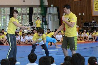 レスリングの構えを指導する高田延彦氏(右)。左端は向井亜紀氏=浦添工業高校体育館