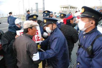 ゲートに進入する工事関係車両を阻止するため県警機動隊ともみ合う市民=キャンプシュワブゲート前、20日午前7時すぎ