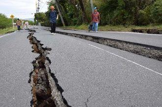 秋津川に沿った道路は亀裂が走りアスファルトがめくれた=16日午後1時5分ごろ、益城町内