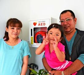 自宅の玄関にAEDを設置した長濱健二さん(右)と長女の妃南ちゃん(中央)、妻の彰乃さん=14日、沖縄市高原