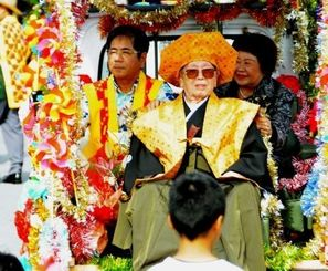 カジマヤーのパレードが、つきしろ自治会で初めて行われ、糸数方建さん(中央)の晴れの日を祝った=28日、南城市