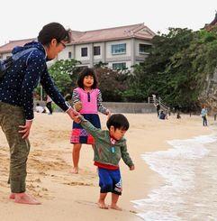 ぽかぽか陽気の中、波打ち際で遊ぶ親子連れ=16日、那覇市若狭の波之上ビーチ(金城健太撮影)