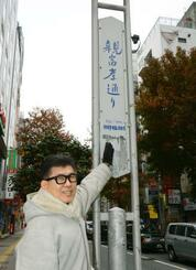 「親富孝通り」の標識を指す、天神・舞鶴親ふこう通り協議会の重孝義会長=14日、福岡市