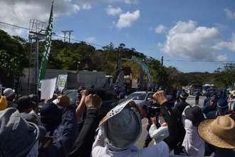 ヘリパッド建設に反対する市民らが抗議する中、N1地区表側の出入り口から入る砂利を積んだトラック=3日午前、東村高江