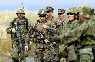 共同訓練を終えた米海兵隊(中央)と陸上自衛隊の水陸機動団の隊員=2018年10月14日、鹿児島県・種子島