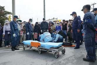 機動隊員に押されて頭を打ち、救急搬送される女性を見守る市民や機動隊員ら=20日午前11時、名護市安和