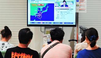 避難所でテレビの台風情報に見入る台湾からの観光客=1日午後8時55分、那覇市役所(下地広也撮影)