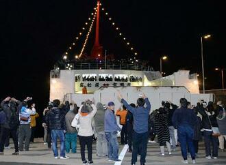 高松港を出港した「宇高航路」の最終便となるフェリーに手を振る人たち=15日夜、高松市