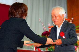 津波津賀子校長(左)から約70年ぶりに卒業証書を受け取った卒業生=13日、那覇市・高良小学校