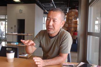 沖縄に来た経緯を話す小川さん。いつも作業するカフェでインタビュー