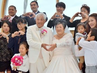 53年ぶりの結婚式を挙げ、家族や友人に祝福される仲間さん夫婦(前列中央)=3日、宜野座村の「ザ・ギノザリゾート美らの協会」