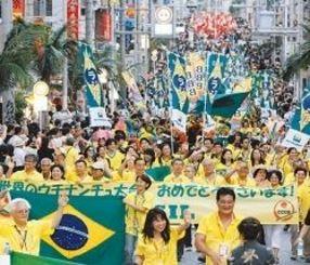 沿道の声援に応えながら行進するブラジル沖縄県人会のメンバーら=10月12日、那覇市・国際通り