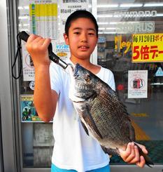 浦添市の小湾川で44センチ、1.43キロのミナミクロダイを釣った福地悠太さん=19日