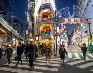 新橋駅に向かう人たち。1都3県を対象に再発令された緊急事態宣言から1週間となった=14日夜、東京都港区