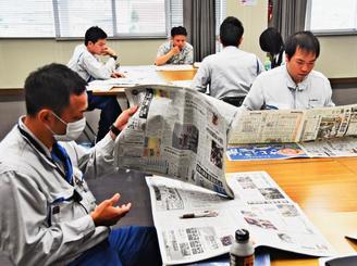 真剣な表情で新聞を読む社員ら=那覇市・沖縄ガス本社