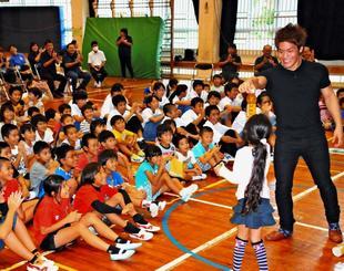 MASAさん(右)のマジックに驚く川平小中の児童生徒ら=7日、石垣市