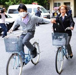 ことし多発している自転車に乗った女性を狙ったひったくりの手口を再現する那覇署員=20日、同署構内