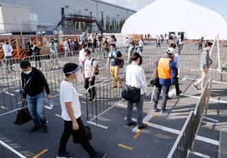 東京五輪・パラリンピックに向けた手荷物検査エリア運営の実証実験で、間隔を空けて列に並ぶ人たち=21日午後、東京都江東区