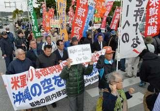 相次ぐ米軍ヘリの事故に抗議する集会参加者=10日、北中城村・米軍キャンプ瑞慶覧の石平ゲート前