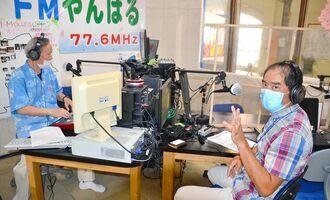 「沖縄タイムス先聞き」に出演した北部支社の粟国雄一郎報道部長(右)とパーソナリティーのあっちゃん=12日、名護市城、「FMやんばる」スタジオ