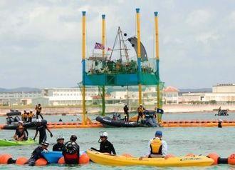 フロート内で台船へ作業をやめるように訴える市民と、市民らをフロートの外へ連れ出す海保職員ら=8日午後12時26分、名護市辺野古沿岸