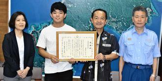 渡具知武豊市長(右から2人目)から感謝状を手渡された渡具知仁来さん(同3人目)=8月27日、名護市役所